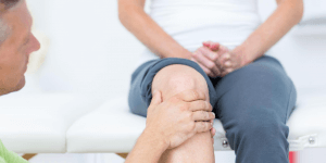 Woman having knee looked at by orthopedic surgeon