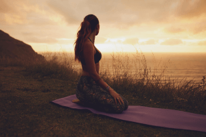 Woman doing yoga outside at sunset