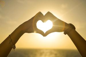 Hands making a heart over sunset
