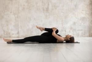 Woman doing knee hugs on floor