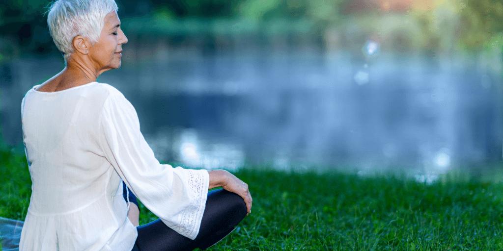 Healthy senior woman meditating outside