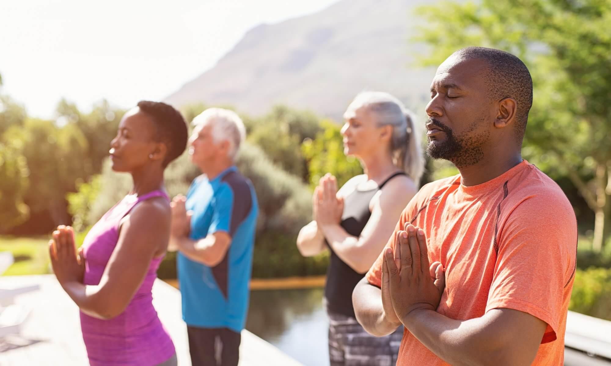 Healthy seniors meditating outside