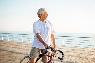 Man overlooking water on bike